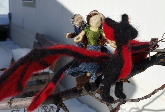 Paul and Jocelyn action figures riding a dragon off to permaculture adventures