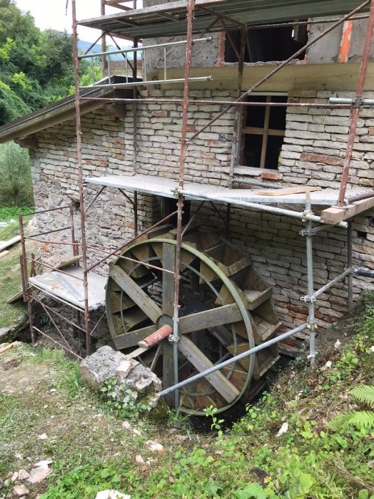 The mill when it was in scaffolding! Building the scaffolding around the waterwheel onto a steep slope wasn't easy!