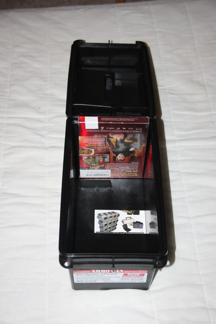 Ammo can open with a DVD case inside for scale